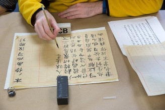 UI Religious Studies PhD candidate Peter Miller tries his hand at Chinese calligraphy at the Mellon Sawyer Chinese scroll workshop, led by British Library conservator emeritus Mark Barnard